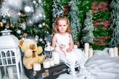 坐在圣诞树附近的一件白色礼服的逗人喜爱的小女孩在手提箱在蜡烛和玩具熊旁边 免版税库存图片