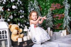 坐在圣诞树附近的一件白色礼服的逗人喜爱的小女孩在手提箱在蜡烛旁边和玩具熊和投掷下雪 图库摄影
