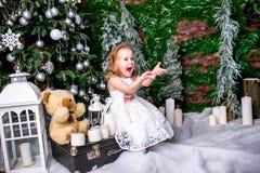 坐在圣诞树附近的一件白色礼服的逗人喜爱的小女孩在手提箱在蜡烛旁边和玩具熊,投掷下雪  免版税图库摄影