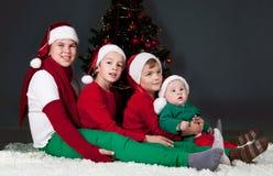 坐在圣诞树附近的四子项。 免版税库存图片
