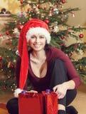 坐在圣诞树附近的圣诞老人帽子的美丽的中年妇女 免版税库存照片