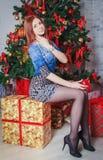 坐在圣诞树附近的女孩 库存图片