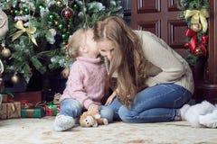 坐在圣诞树附近的妇女和孩子 图库摄影