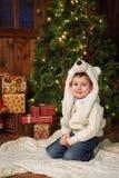 坐在圣诞树附近的小男孩 库存照片