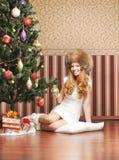 坐在圣诞树附近的帽子的一个十几岁的女孩 免版税库存照片