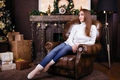 坐在圣诞树附近的愉快的少妇全长画象  免版税库存照片
