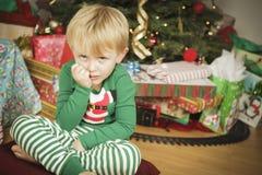 坐在圣诞树附近的新脾气坏的男孩 免版税库存照片
