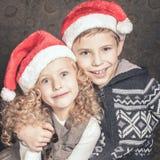 坐在圣诞树附近的滑稽的孩子 佩带的圣诞老人帽子 免版税库存图片