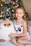 坐在圣诞树附近的美丽的小女孩 图库摄影