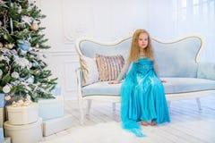 坐在圣诞树附近的逗人喜爱的女孩 免版税库存图片