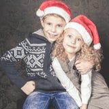坐在圣诞树附近的滑稽的孩子 佩带的圣诞老人帽子 免版税库存照片