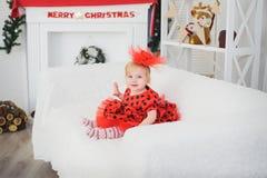 坐在圣诞节壁炉附近的婴孩 水平 免版税图库摄影