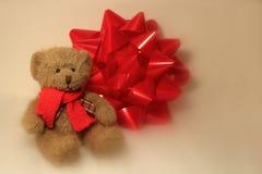 坐在圣诞节弓旁边的玩具熊 免版税库存照片