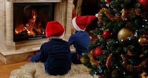 坐在圣诞节的壁炉附近的两个逗人喜爱的孩子装饰了室 免版税库存图片