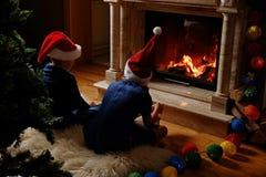坐在圣诞节的壁炉附近的两个逗人喜爱的孩子装饰了室 免版税图库摄影