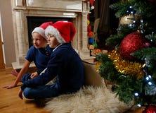 坐在圣诞节的壁炉附近的两个逗人喜爱的孩子装饰了室 库存照片