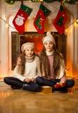 坐在圣诞节的装饰的壁炉旁边的两个逗人喜爱的女孩 库存图片