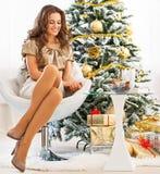 坐在圣诞节附近的愉快的少妇全长画象  免版税库存图片