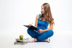 坐在地板和写笔记的女孩 免版税库存图片