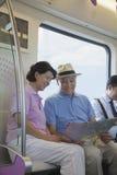 坐在地铁和看地图的成熟夫妇 免版税库存图片