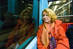 坐在地铁的妇女在晚上 免版税库存图片