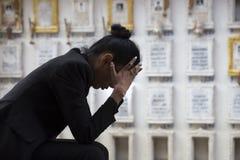 坐在坟墓附近的哀伤的妇女 免版税库存图片