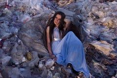坐在垃圾中山的一个老篮子的礼服的女孩在垃圾填埋的 免版税库存照片