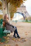 坐在埃佛尔铁塔附近的小姐 免版税库存照片