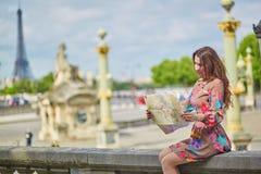 坐在埃佛尔铁塔附近的少妇在巴黎 免版税库存照片