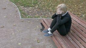坐在城市公园的美丽的哀伤的妇女 影视素材