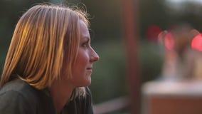 坐在城市咖啡馆的可爱的微笑的少妇 特写镜头,被弄脏的光,都市街道,侧视图 影视素材