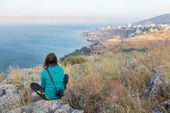坐在城市湖背面图上的妇女摄影师 库存图片