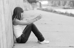 坐在城市环境里的孤独的女孩 免版税库存图片