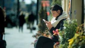 坐在城市街道的一条长凳和使用她巧妙的电话的美丽的妇女 股票录像