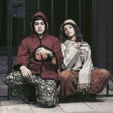 坐在城市街道的年轻时尚行家夫妇 免版税库存图片