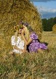 坐在域的一个干草堆附近的女孩 免版税库存图片