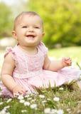 坐在域的夏天礼服的女婴 免版税库存图片