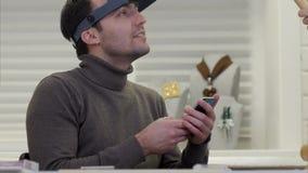 坐在堆的珠宝商金刚石前面谈话与某人有手机的在他的手上 股票视频