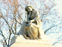 坐在墓石顶部的一个沉思雕象 免版税库存图片
