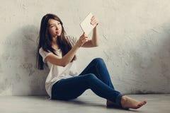 坐在墙壁和神色附近的女孩在片剂 库存照片
