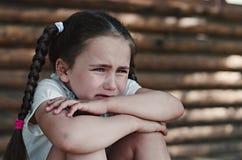 坐在墙壁附近的生气小女孩 免版税库存图片