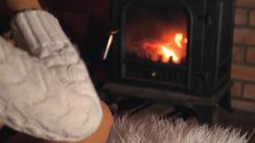 坐在壁炉和饮用的酒前面的孤独的妇女从玻璃 股票录像