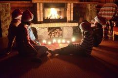 坐在壁炉附近和庆祝圣诞节和新年、父母和孩子圣诞老人帽子的愉快的家庭 免版税库存图片