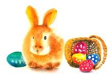 坐在复活节彩蛋旁边篮子的逗人喜爱的复活节兔子  免版税库存图片