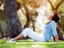 坐在夏天公园的美丽的妇女 免版税库存图片