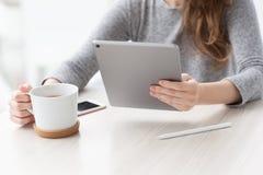 坐在夏天咖啡馆的妇女喝拿着片剂计算机的茶 免版税库存照片