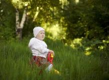 坐在夏天的愉快的小女孩 免版税库存照片