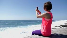 坐在多岩石的海滩藏品电话和照相的年轻美丽的白种人妇女 股票视频