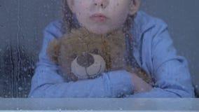 坐在多雨窗口后的小女性孤儿拥抱玩具熊和作梦 股票录像