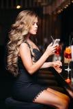 坐在夜总会测试鸡尾酒和等待的会议的性感的妇女 库存图片
